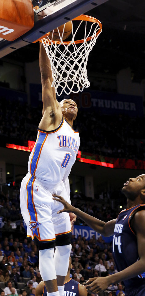 Oklahoma City's Russell Westbrook (0) dunks the ball over Michael Kidd-Gilchrist (14) during an NBA basketball game between the Oklahoma City Thunder and Charlotte Bobcats at Chesapeake Energy Arena in Oklahoma City, Monday, Nov. 26, 2012.  Photo by Nate Billings , The Oklahoman
