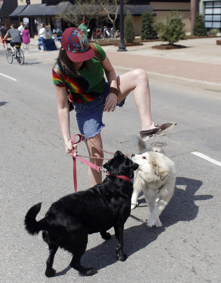 Photo - Christine Windham  untangles herself with her dogs Moxie, a Great Pyrenees mic and Bayla, a lab mix,  at Open Streets OKC, along NW 23rd Street between Robinson and Western, Sunday, March 22, 2015. Photo by Doug Hoke, The Oklahoman