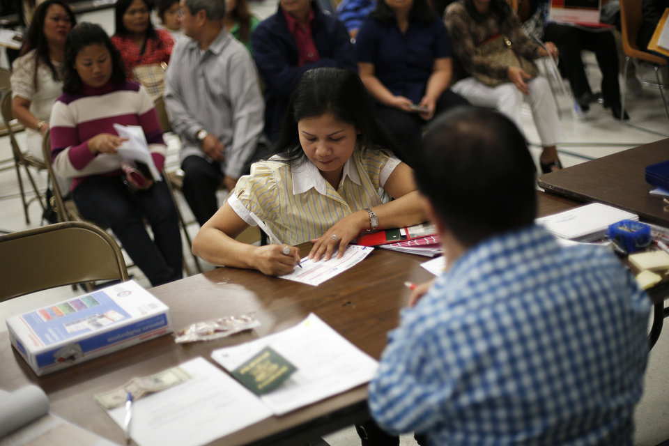 Merlyn Labarn, of Oklahoma City, fills out forms to renew her passport during a visit from a delegation of the Philippine consulate in Chicago.