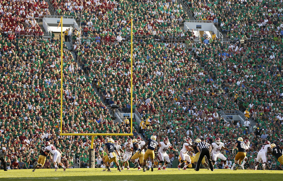 Photo - The Sooners and Fighting Irish play in the third quarter during a college football game between the University of Oklahoma and the Notre Dame at Notre Dame Stadium in South Bend, Ind., Saturday, Sept. 28, 2013. OU won, 35-21. Photo by Nate Billings, The Oklahoman