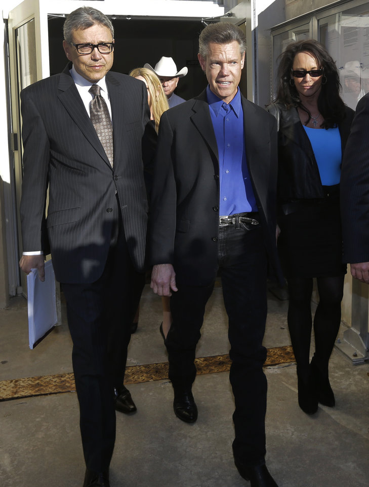 Photo - Entertainer Randy Travis, center, exits Grayson County Courthouse with his lawyer Larry Friedman, left, and an unidentified person, right, Thursday, Jan. 31, 2013, in Sherman, Texas. Travis plead guilty to driving while intoxicated in a plea agreement with the court and will pay a $2,000 fine and serve a two year probation. (AP Photo/Tony Gutierrez)