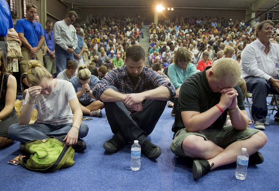 Photo - Mourners bow their heads in prayer during a memorial service, Monday, July 1, 2013 in Prescott, Ariz. The service was held for the 19 Granite Mountain Hotshot Crew firefighters who were killed Sunday, when an out-of-control blaze overtook the elite group.  (AP Photo/Julie Jacobson)