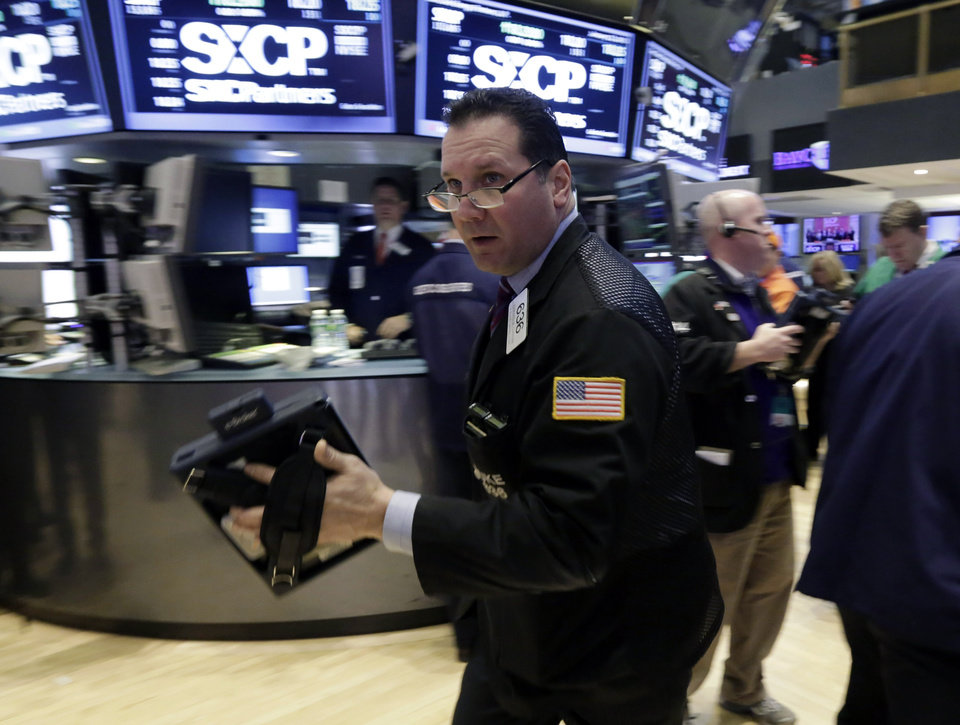 Trader Edward Curran scurries across the floor of the New York Stock Exchange Tuesday, Jan. 22, 2013. Stocks are wavering in early trading on Wall Street as U.S. companies turn in a mixed batch of earnings reports. (AP Photo/Richard Drew)