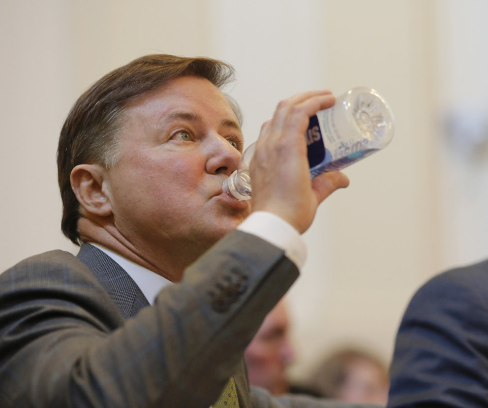 Photo - Challenger Gentner Drummond drinks water during the hearing. Oklahoma Attorney General Mike Hunter can remain on the ballot after the Oklahoma Election Board voted 3-0 on Monday, April 23, 2018, to deny a challenge to his candidacy on residency grounds. Hunter, a Republican, testified he always kept Oklahoma as his permanent home even though he lived in Virginia for years while working in Washington, D.C. for two trade organizations.