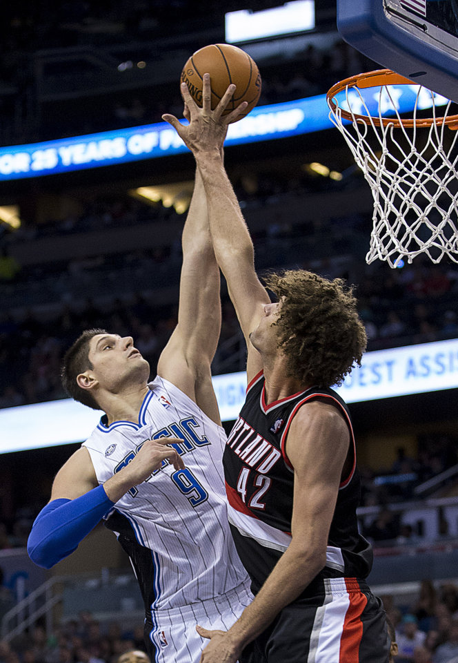 Photo - Orlando Magic's Nikola Vucevic (9) shoots over  Portland Trail Blazers' Robin Lopez (42) during the first half of an NBA basketball game in Orlando, Fla., Tuesday, March 25, 2014. (AP Photo/Willie J. Allen Jr.)