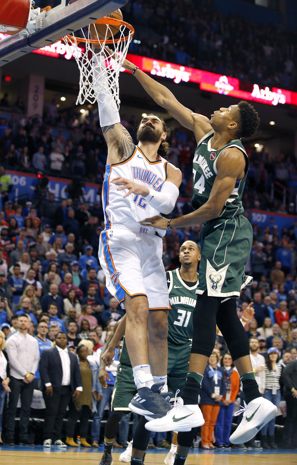 Photo -  Oklahoma City's Steven Adams dunks over Milwaukee's Giannis Antetokounmpo  during Friday's game. [Photo by Sarah Phipps, The Oklahoman]