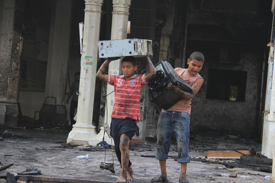Photo - Egyptian children carry computer equipment in the burned remains of the Rabaah al-Adawiya mosque, in the center of the largest protest  camp of supporters of ousted President Mohammed Morsi, that was cleared by security forces, in the district of Nasr city, Cairo, Egypt. The death toll keeps going up in Egypt after security forces swept through two sit-in sites yesterday, operated by supporters of Morsi. An Egyptian Health Ministry spokesman now says over 400 people died in the violence that has prompted international criticism. (AP Photo/Ahmed Gomaa)