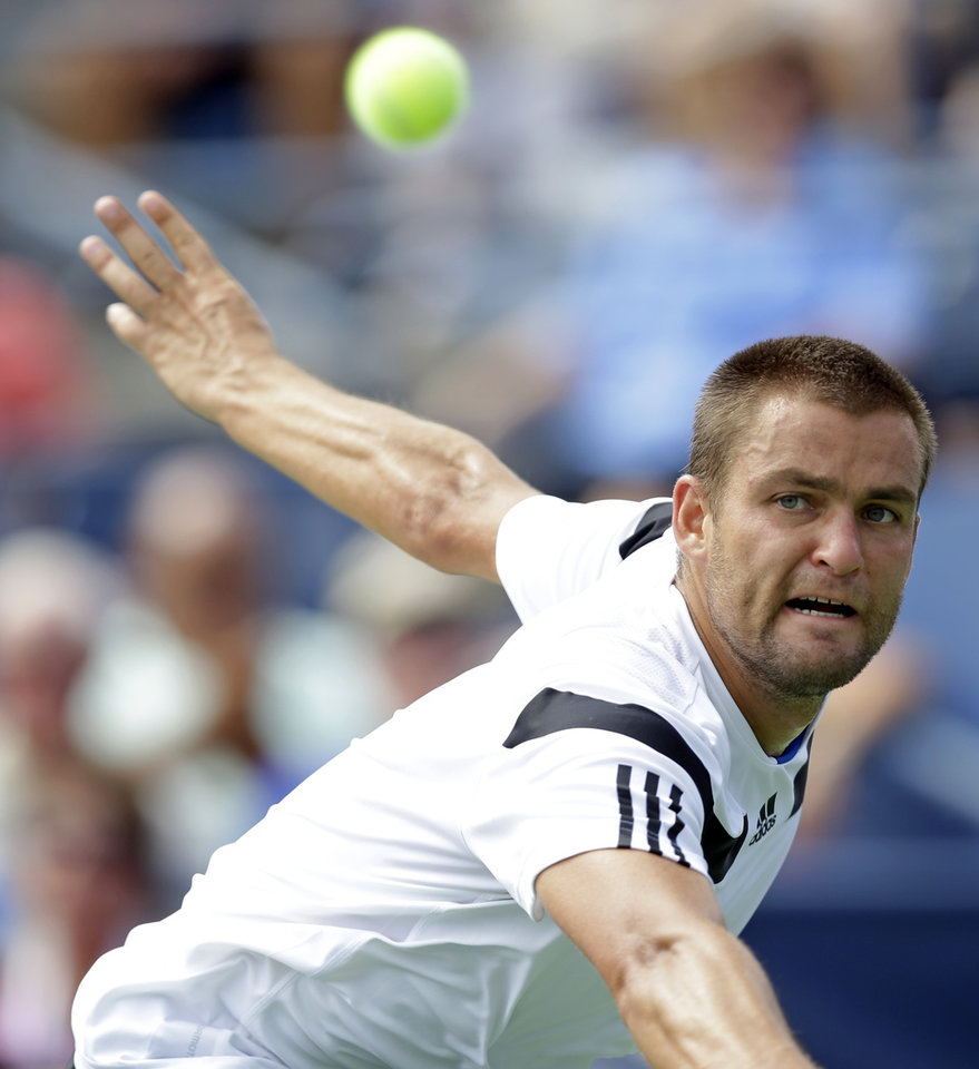 Photo - Mikhail Youzhny, of Russia, returns a shot to Lleyton Hewitt, of Australia, during the fourth round of the 2013 U.S. Open tennis tournament, Tuesday, Sept. 3, 2013, in New York. (AP Photo/Kathy Willens)