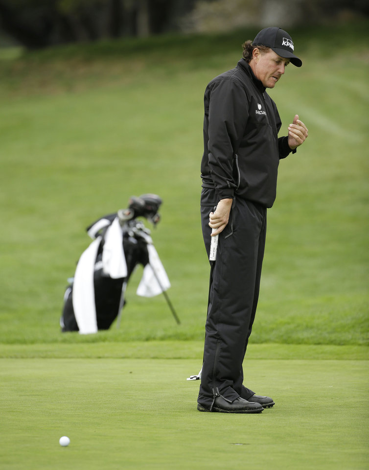 Photo - Phil Mickelson reacts after missing a birdie putt on the first green during the final round of the AT&T Pebble Beach Pro-Am golf tournament, Sunday, Feb. 9, 2014, in Pebble Beach, Calif. (AP Photo/Eric Risberg)