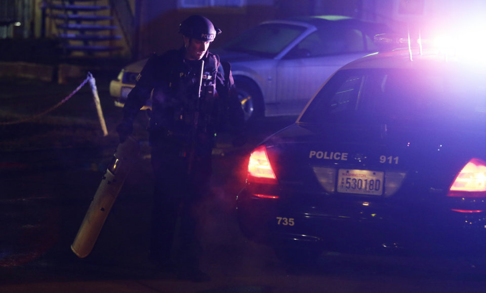 Photo - A Tukwila Police officer walks with his weapon and a shield after returning to his car near the scene of an overnight shooting that left five people dead, Monday, April 22, 2013, at an apartment complex in Federal Way, Wash. (AP Photo/Ted S. Warren)