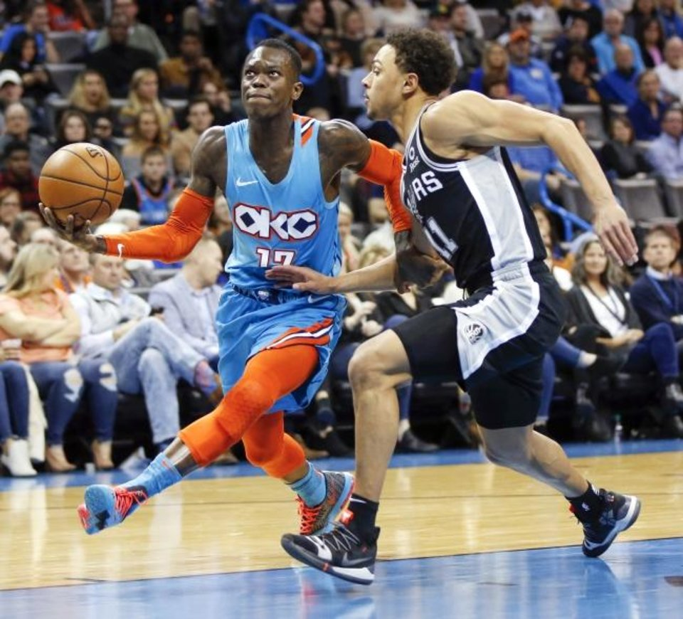 Photo - Oklahoma City's Dennis Schroder (17) drives to the basket against San Antonio's Bryn Forbes (11) during an NBA basketball game between the San Antonio Spurs and the Oklahoma City Thunder at Chesapeake Energy Arena in Oklahoma City, Saturday, Jan. 12, 2019. Oklahoma City won 122-112. Photo by Nate Billings, The Oklahoman