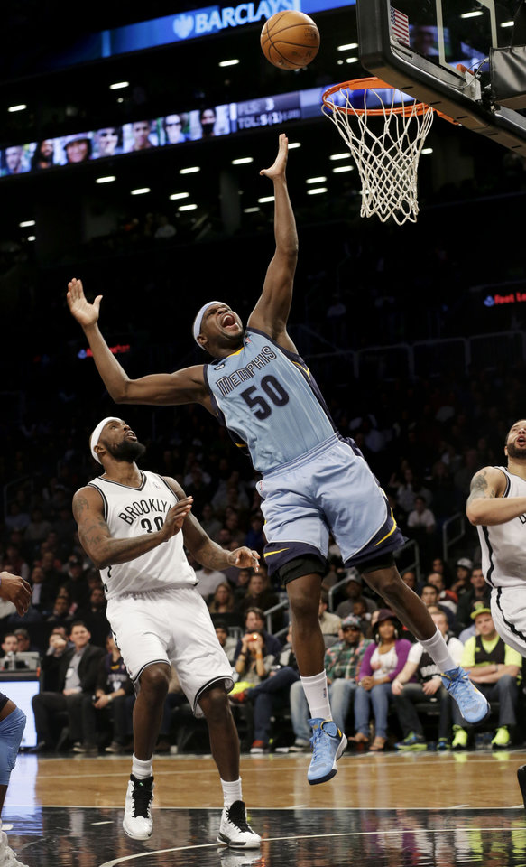 Memphis Grizzlies' Zach Randolph, center, is fouled by Brooklyn Nets' Deron Williams, right, while Reggie Evans looks on during the first half of the NBA basketball game at the Barclays Center Sunday, Feb. 24, 2013 in New York.  (AP Photo/Seth Wenig)