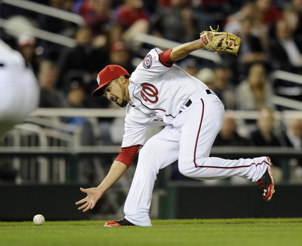 Photo - Washington Nationals third baseman Anthony Rendon fields a bunt by Miami Marlins' Reed Johnson during the seventh inning of a baseball game, Tuesday, April 8, 2014, in Washington. Johnson was out at first on the play. The Nationals won 5-0. (AP Photo/Nick Wass)