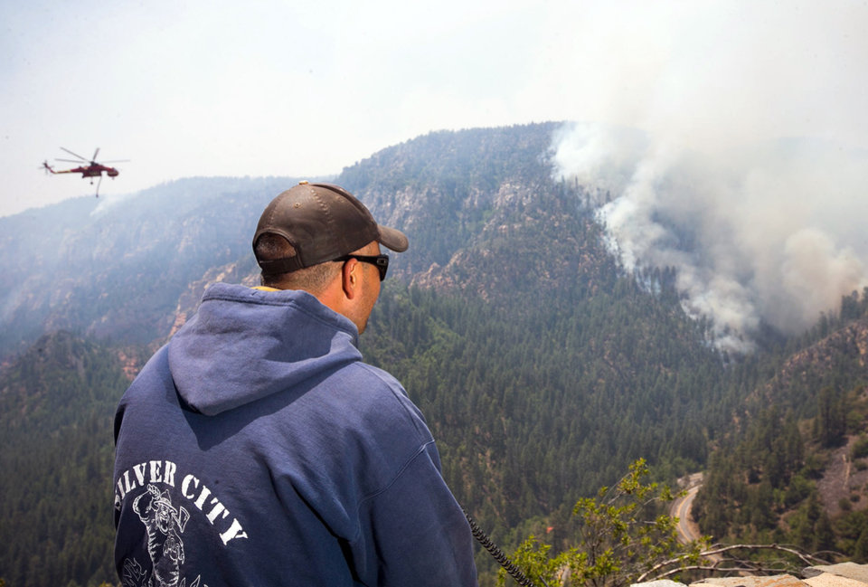 Photo - A Sante Fe Hot Shot works as a lookout as he oversees part of the Slide Fire in Sterling Canyon at the Oak Creek Overlook above Sedona, Ariz., on Thursday, May 22, 2014. Hundreds of firefighters worked Thursday to protect communities on the edge of Flagstaff from a wildfire that is chewing up a scenic Arizona canyon with towering flames and burning entire trees down to nothing but ash. (AP Photo/The Arizona Republic, Michael Schennum)  MARICOPA COUNTY OUT; MAGS OUT; NO SALES