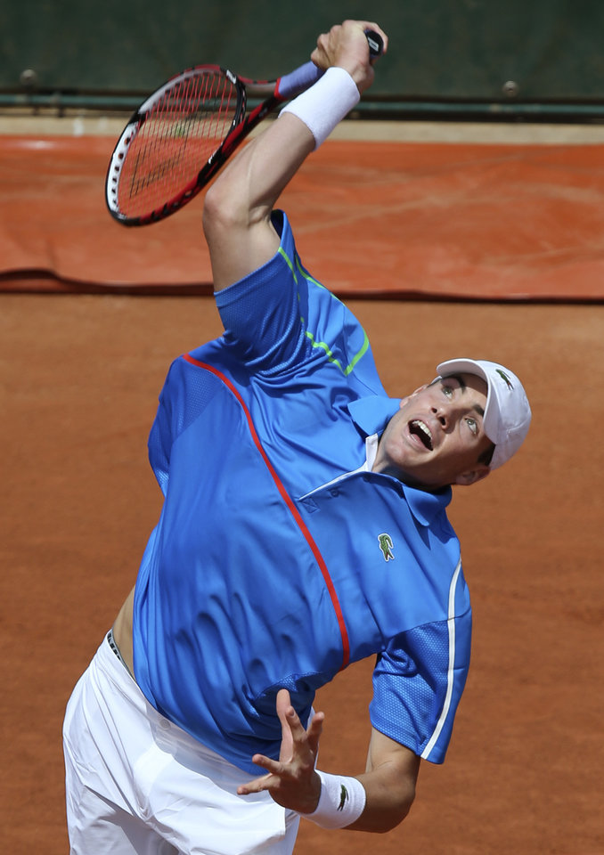 Photo - USA's John Isner serves to France's Pierre-Hugues Herbert during their first round match of  the French Open tennis tournament at the Roland Garros stadium, in Paris, France, Sunday, May 25, 2014. (AP Photo/David Vincent)