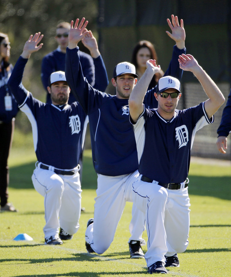 Photo - Detroit Tigers pitcher Max Scherzer, right, Drew VerHagen, center, and Robbie Ray, left,  warm up on the team's first day of baseball spring training for pitchers and catchers in Lakeland, Fla., Friday, Feb. 14, 2014. (AP Photo/Gene J. Puskar)
