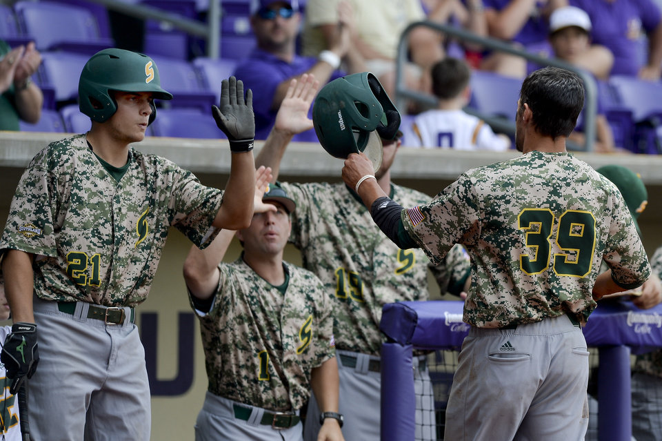 Photo - Southeastern Louisiana's Jacob Seward (39) is greeted by teammate Daniel Midyett (21) in the dugout after scoring against Bryant on Saturday, May 31, 2014, during the first round of an NCAA college baseball regional tournament in Baton Rouge, La. (AP Photo/The Baton Rouge Advocate, Hilary Scheinuk) NO SALES; MAGAZINES OUT; INTERNET OUT;TV OUT; NO FOREIGNS. LOUISIANA BUSINESS INC. OUT (INCLUDING GREATER BATON ROUGE BUSINESS REPORT; 225; 10/12; INREGISTER; LBI CUSTOM MAGS OUT/  INTERNET OUT/ ONLINE OUT/ NO SALES/  TV OUT/  FOREIGN OUT/ LOUISIANA BUSINESS INC. OUT (INCLUDING GREATER BATON ROUGE BUSINESS REPORT, 225, 10/12, INREGISTER, LBI CUSTOM PUBLICATIONS) MANDATORY CREDIT THE ADVOCATE