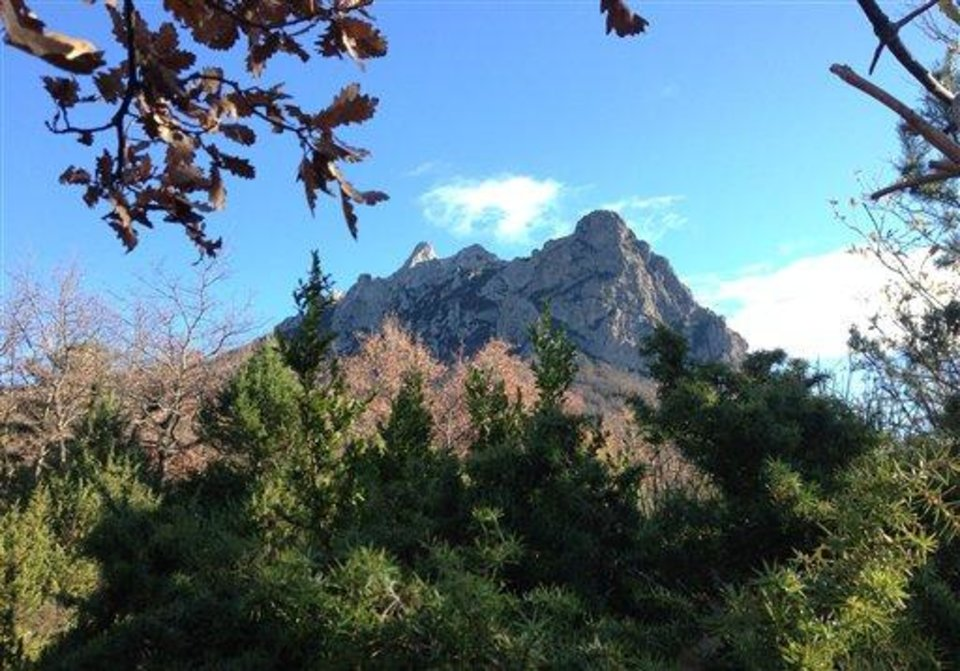 Photo - Foliage frames the Bugarach mountain peak in southern France, Monday, Dec. 10, 2012.  From Russia to California, thousands are preparing for the fateful day, when many believe a 5,125-year cycle known as the Long Count in the Mayan calendar supposedly comes to an end.  The Internet has helped feed the frenzy, spreading rumors that a mountain in the French Pyrenees is hiding an alien spaceship that will be the sole escape from the destruction.  French authorities are blocking access to Bugarach peak from Dec. 19-23 except for the village's 200 residents