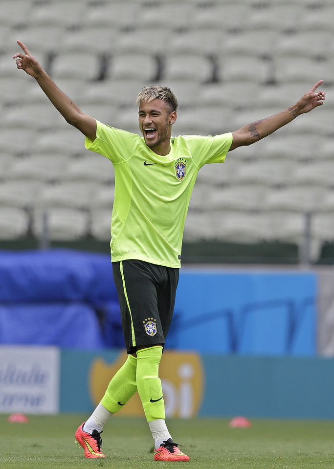 Photo - Brazil's Neymar raises his arms during a training session at the Arena Castelao in Fortaleza, Brazil, Monday, June 16, 2014. Brazil plays in group A of the 2014 soccer World Cup. (AP Photo/Andre Penner)