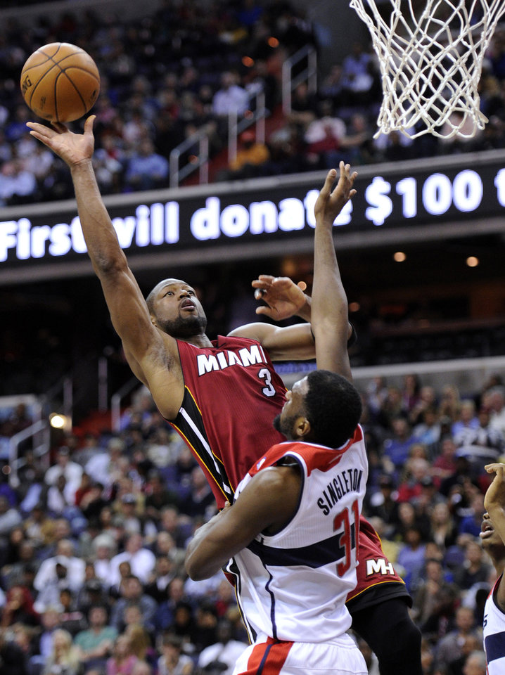 Photo - Miami Heat guard Dwyane Wade (3) takes a shot against Washington Wizards forward Chris Singleton (31) during the first half of an NBA basketball game, Tuesday, Dec. 4, 2012, in Washington. (AP Photo/Nick Wass)