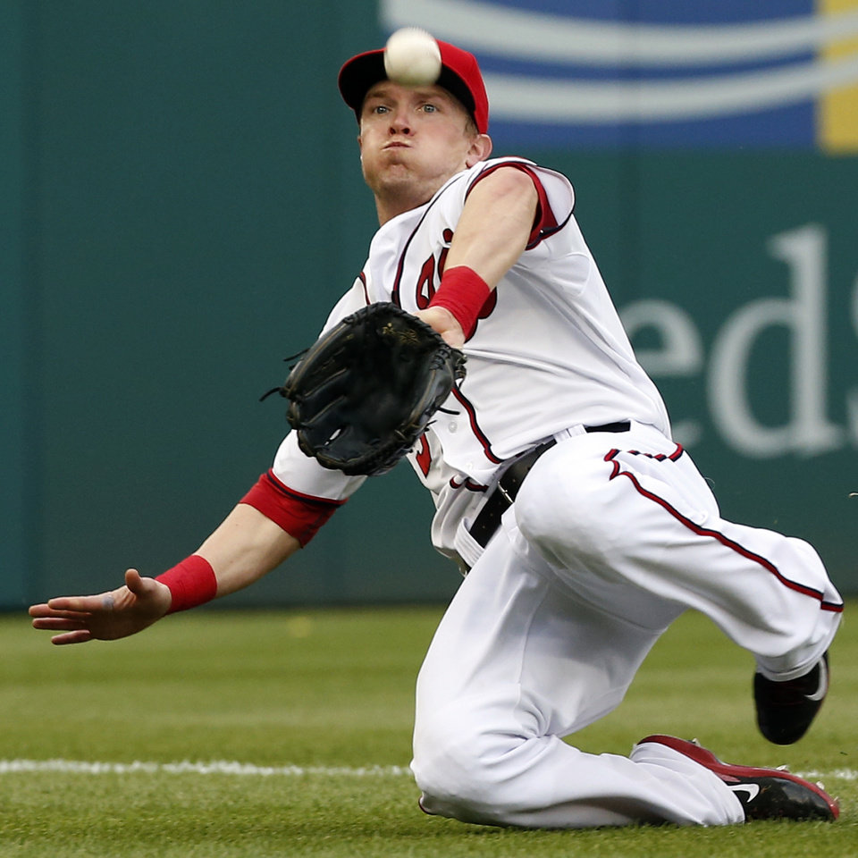 Photo - Washington Nationals left fielder Nate McLouth slides to catch a foul ball hit by Cincinnati Reds' Billy Hamilton during the fifth inning of a baseball game at Nationals Park Wednesday, May 21, 2014, in Washington. (AP Photo/Alex Brandon)