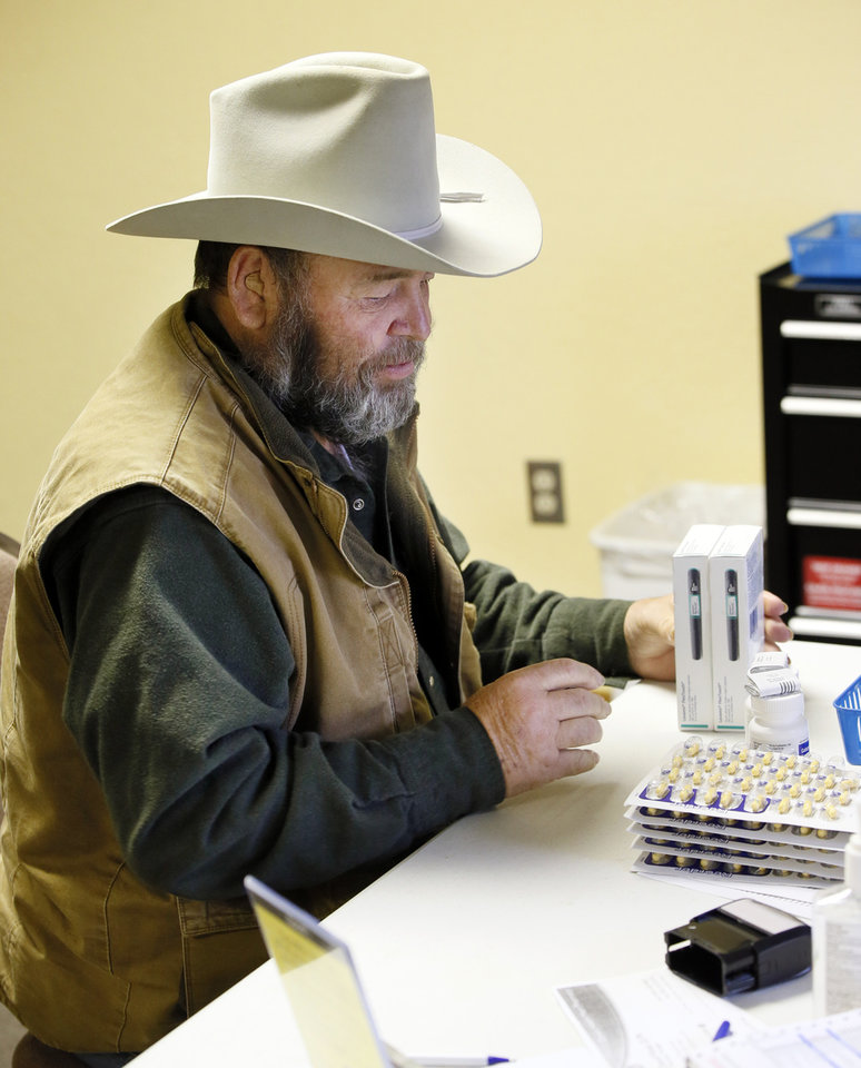 Photo -  Forrest Barrett, of Cushing, checks his medications after visiting the pharmacy during the Hope Medical Clinic at the Slaughterville Baptist Church. [PHOTO BY NATE BILLINGS, THE OKLAHOMAN]