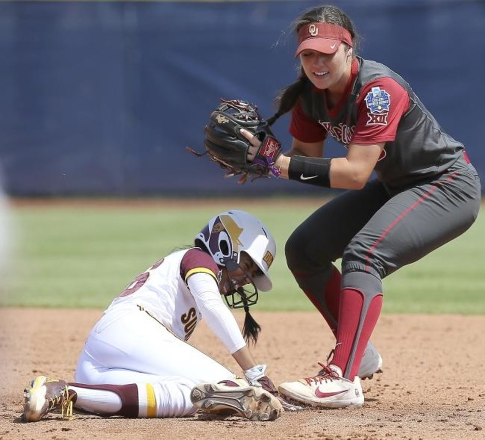 Photo - Arizona State's Taylor Becerra (26) grimaces after hitting Oklahoma's Caleigh Clifton (20) while sliding to second base in the first inning of the Women's College World Series game between the University of Oklahoma (OU) and Arizona State at USA Softball Hall of Fame Stadium in Oklahoma City, Saturday, June 2, 2018. Photo by Bryan Terry, The Oklahoman