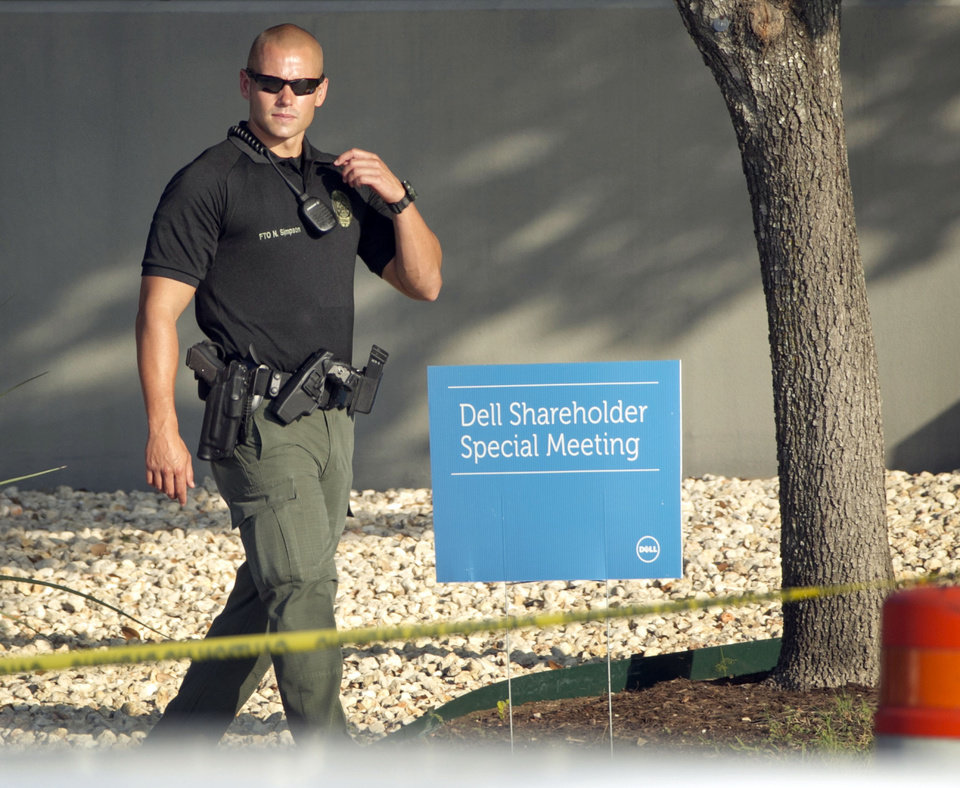 Photo - A Round Rock, Texas, police officer guards the Dell shareholders meeting at Dell headquarters in Round Rock, Texas on Thursday, Sept. 12, 2013.  The majority of Dell shareholders voted in favor of a $25 billion buyout offer led by company founder and CEO Michael Dell.  (AP Photo/Austin American-Statesman, Jay Janner)