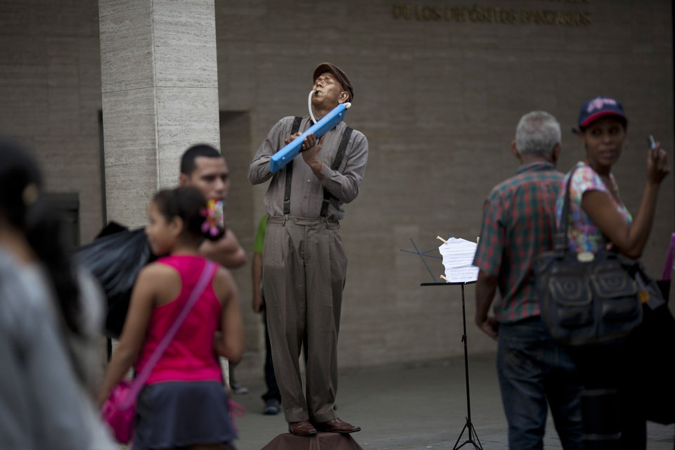 Photo - A street artist plays an instrument as he impersonates a mannequin, one day before state elections for governors and legislators, in Caracas, Venezuela, Saturday, Dec. 15, 2012. If candidates who support Venezuela's President Hugo Chavez gain or even hold steady Sunday, the executive branch could strengthen its hold on the grass roots, as communal councils decide, often based on loyalty, such questions as who gets a new roof, or who receives vocational training, distributing the funds directly. (AP Photo/Ariana Cubillos)