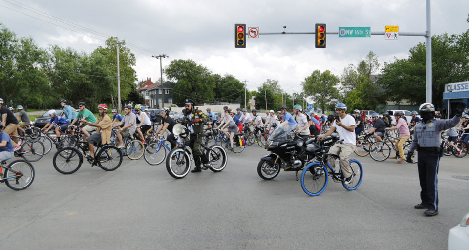 Photo - Dozens of bicyclists ride along Classen Boulevard Tuesday, May 7, 2019, to highlight the need for better bike lanes, stopping at 16th and Classen Blvd. where a ghost bike memorial for Chad Epley who was killed at the intersection while riding home after work, and then traveling on to the Tower Theater.  Photo by Doug Hoke.