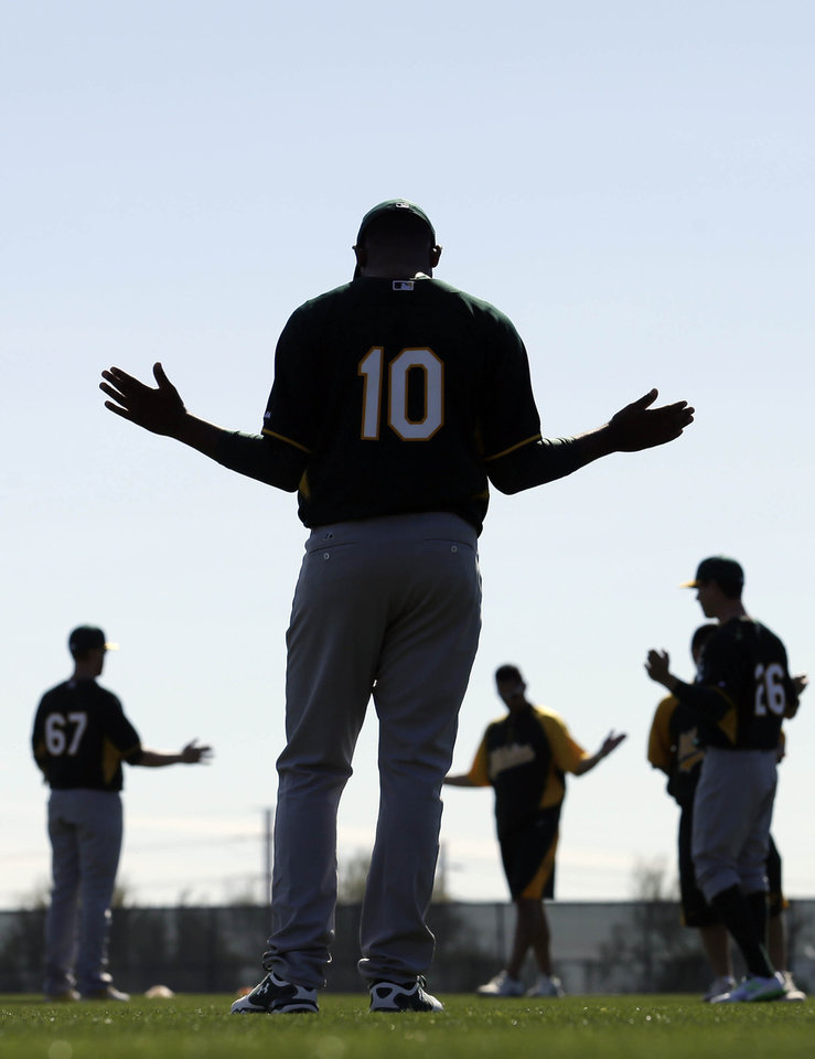 Photo - Oakland Athletics infielder Daric Barton, center, stretches during spring training baseball practice Saturday, Feb. 15, 2014, in Scottsdale, Ariz.  (AP Photo/Gregory Bull)