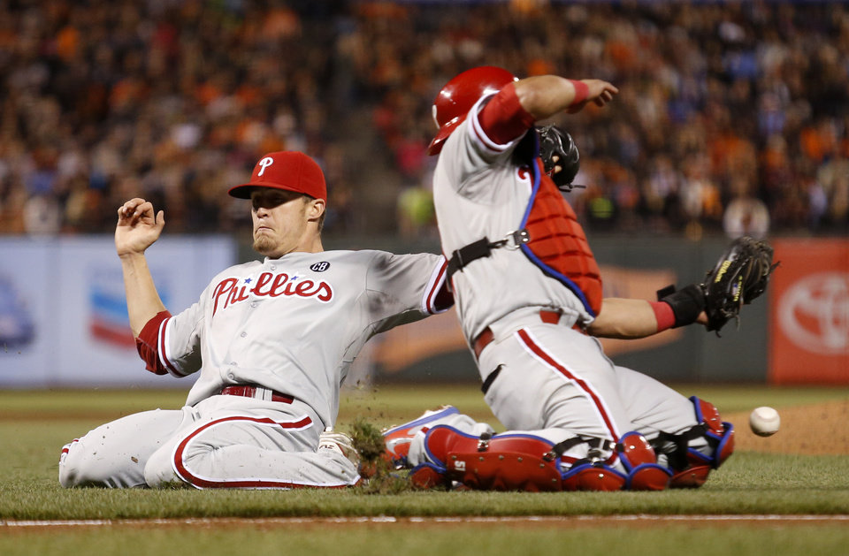 Photo - Philadelphia Phillies pitcher Ken Giles, left, and catcher Carlos Ruiz are unable to catch an infield fly ball hit by San Francisco Giants' Gregor Blanco during the eighth inning of a baseball game, Friday, Aug, 15, 2014, in San Francisco. (AP Photo/Beck Diefenbach)