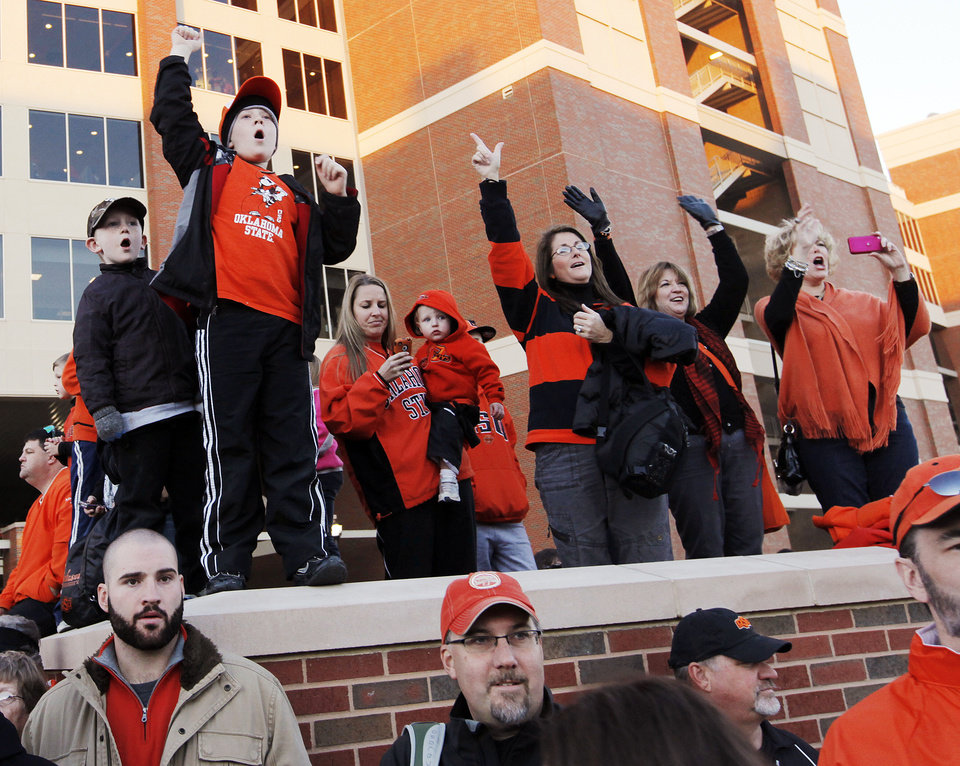 Photo - OSU fans cheer during the Spirit Walk before the Bedlam college football game between the University of Oklahoma Sooners (OU) and the Oklahoma State University Cowboys (OSU) at Boone Pickens Stadium in Stillwater, Okla., Saturday, Nov. 27, 2010. Photo by Nate Billings, The Oklahoman