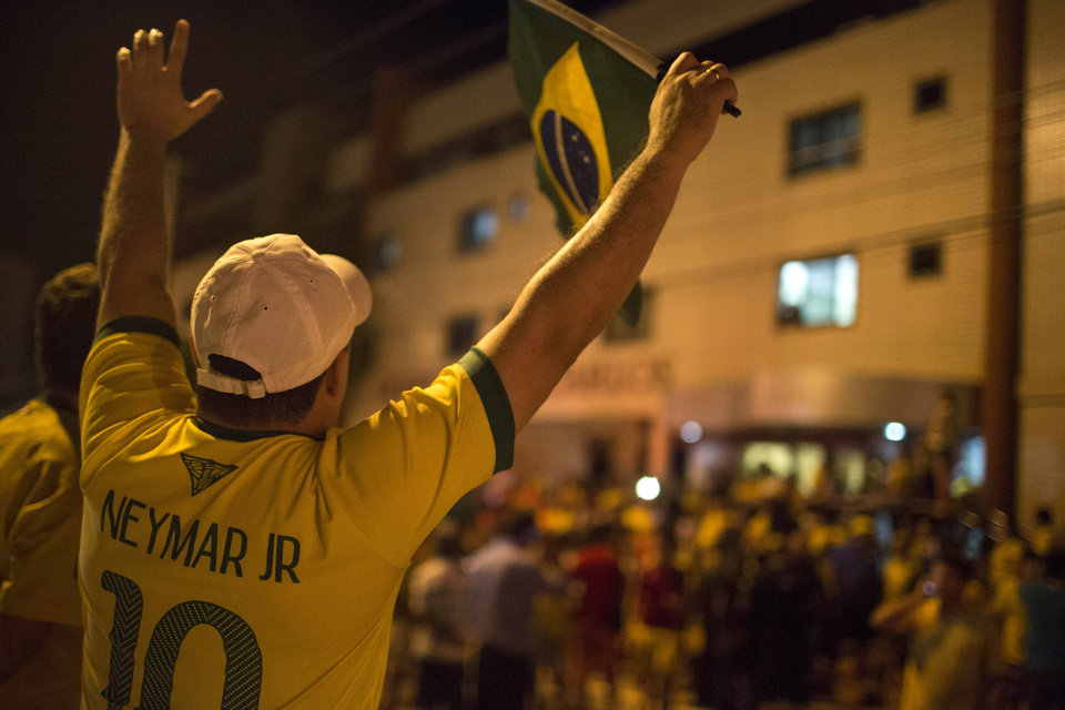 Photo - A Brazil soccer fan wearing a Neymar jersey waves a Brazilian flag outside Sao Carlos Hospital where Brazil's soccer player Neymar was taken after being injured during the World Cup quarterfinal soccer match against Colombia in Fortaleza, Brazil, Friday, July 4, 2014. Brazil's team doctor says Neymar will miss the rest of the World Cup after breaking a vertebrae during the team's quarterfinal win over Colombia. (AP Photo/Renata Brito)