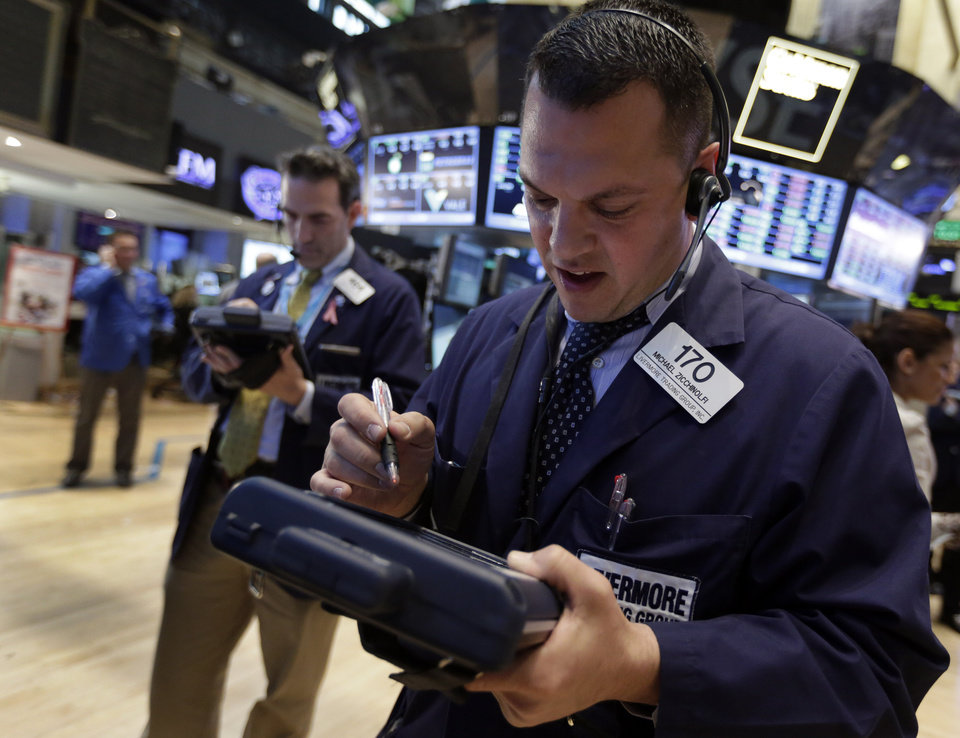 Photo - Trader Michael Zicchinolfi, right, works on the floor of the New York Stock Exchange Tuesday, May 7, 2013. The Dow Jones industrial average punched through another milestone Tuesday: its first close above 15,000. (AP Photo/Richard Drew)