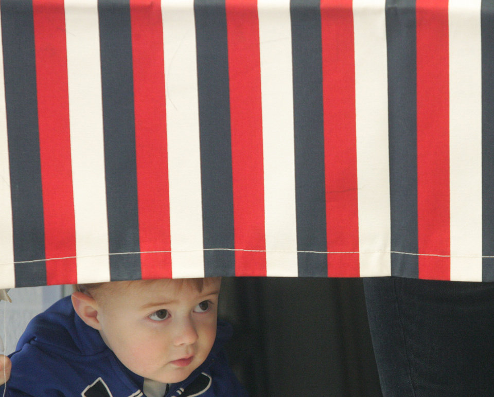 Photo -   Chandler Lorimer, 2, Galena, peeks out under the voting curtain while at Galena City Hall in Galena, Kan., while his mother Jamie votes on Tuesday, Nov. 6, 2012. (AP Photo/The Joplin Globe, Roger Nomer)