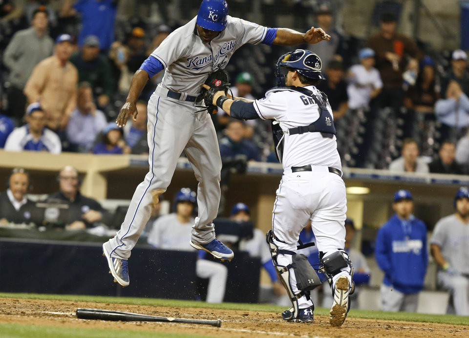 Photo - San Diego Padres catcher Yasmani Grandal puts tag on Kansas City Royals' Lorenzo Cain who is out trying to score from third on an infield grounder in the 11th inning of a baseball game Monday, May 5, 2014, in San Diego.  (AP Photo/Lenny Ignelzi)