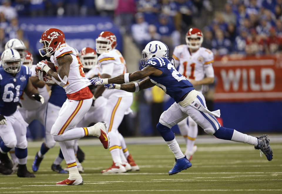 Photo - Kansas City Chiefs wide receiver Dwayne Bowe (82) runs out of the grasp of Indianapolis Colts cornerback Greg Toler (28) during the first half of an NFL wild-card playoff football game Saturday, Jan. 4, 2014, in Indianapolis. (AP Photo/AJ Mast)