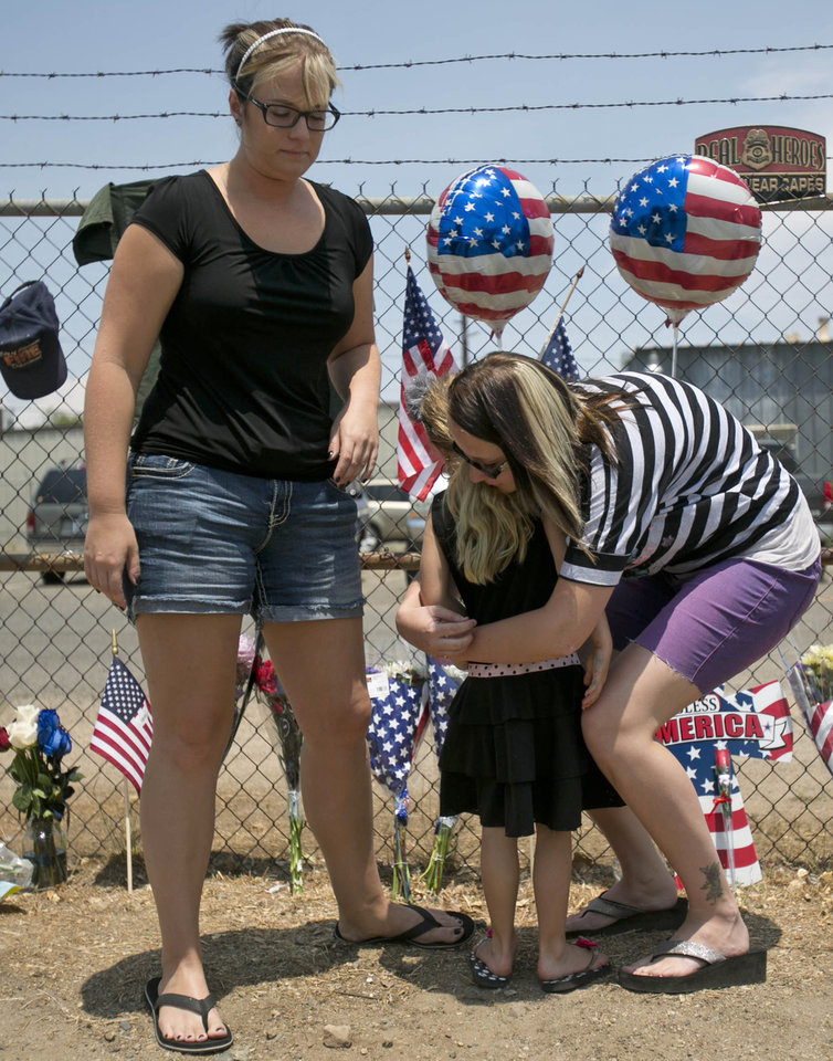 Photo - Angela Clark, left, her daughter Chloe, middle, and Theresa Winquest visit a makeshift memorial at the fire station Monday, July 1, 2013, in Prescott, Ariz., where an elite team of firefighters was based. Nineteen of the 20 members of the team were killed Sunday when a wildfire suddenly swept toward them in Yarnell, Ariz. (AP Photo/The Arizona Republic, Patrick Breen)