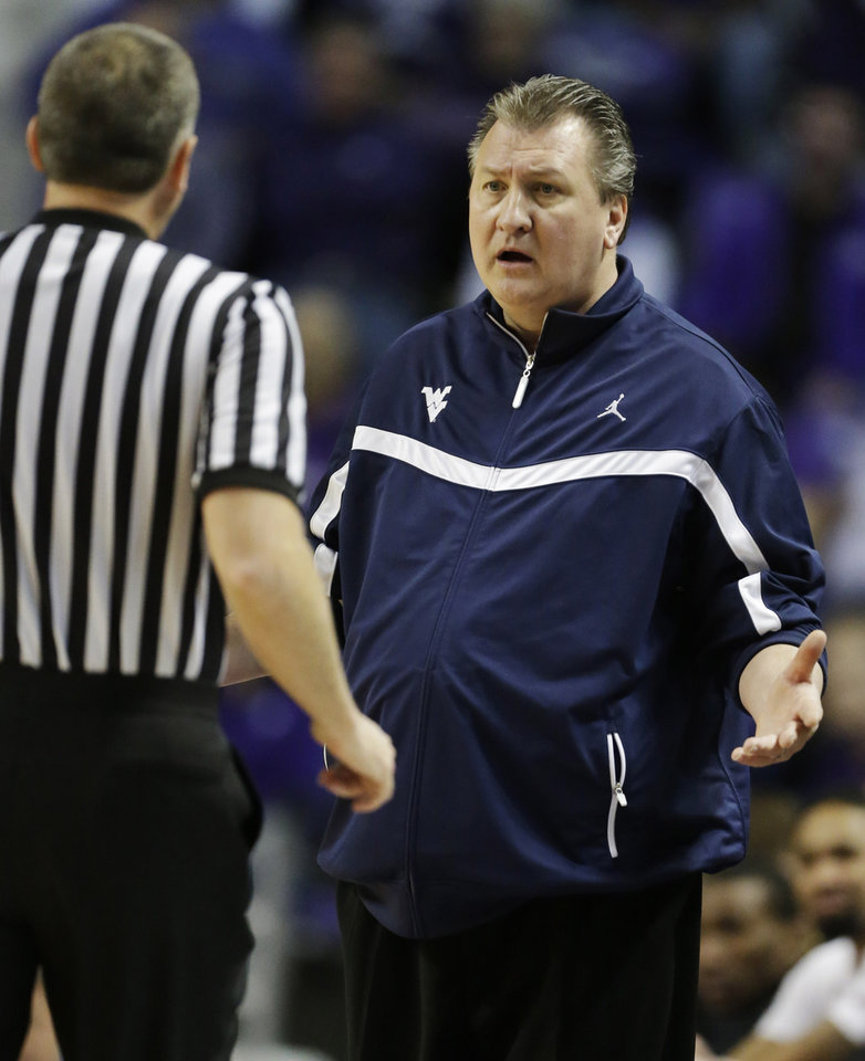 Photo - West Virginia head coach Bob Huggins, right, talks with an official during the first half of an NCAA college basketball game against Kansas State in Manhattan, Kan., Monday, Feb. 18, 2013. (AP Photo/Orlin Wagner)