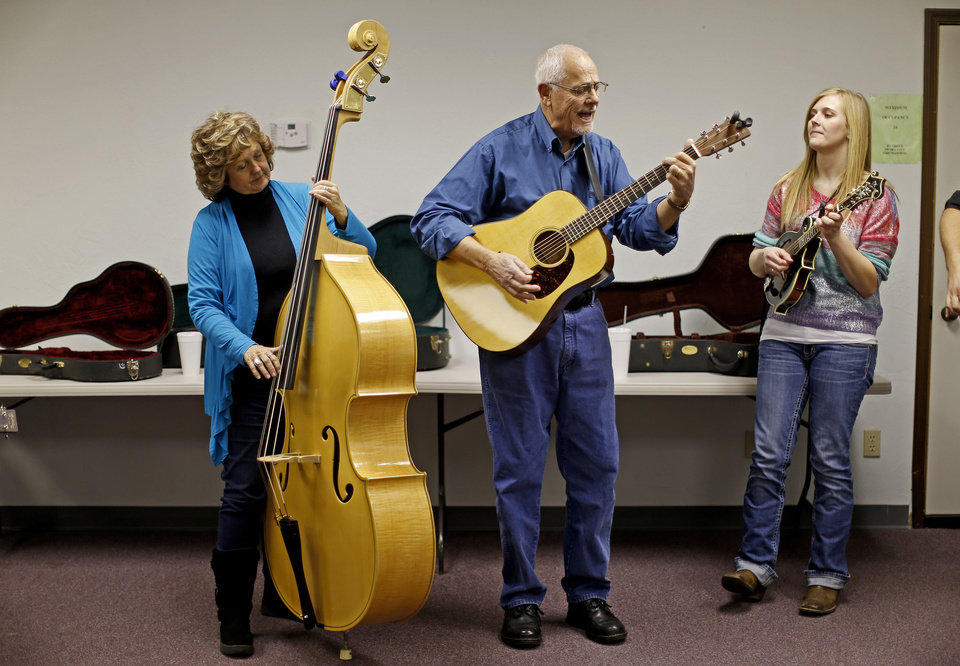 Photo - Jan Hickman, left, of Shawnee, Tom Cole, of Norman, and Kaitlyn Horn with the band Heartbreak Line play during a bluegrass jam session in Del City.  Photos by Bryan Terry, The Oklahoman