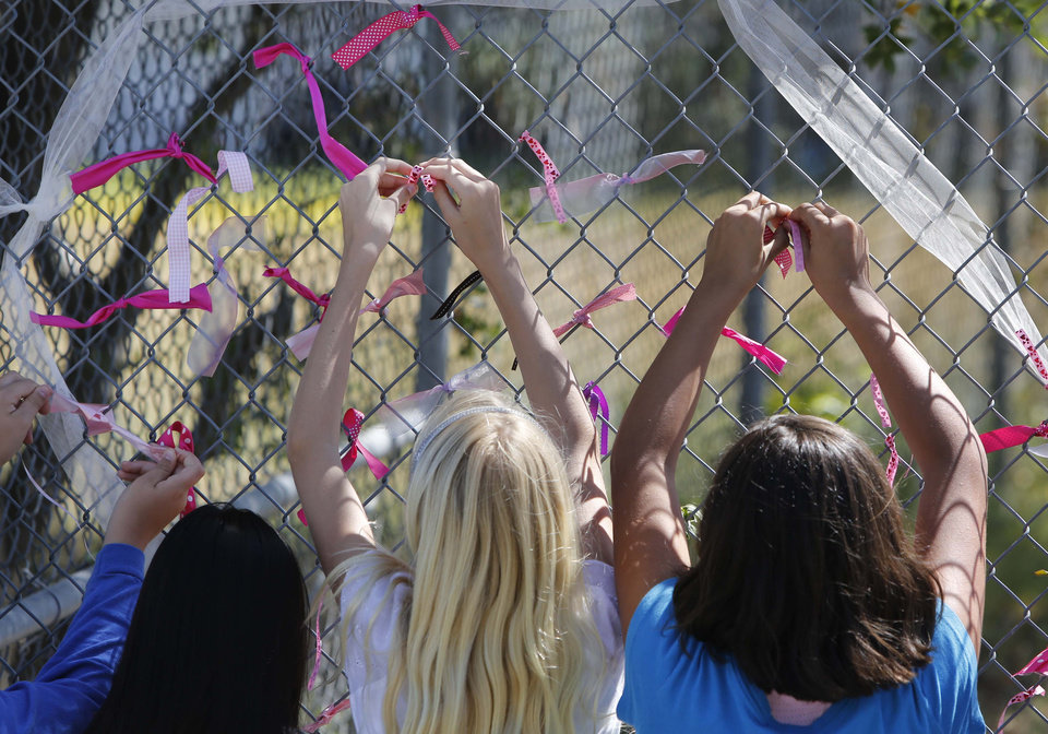 Photo - Students at Jenny Lind Elementary School tie ribbons honoring murder victim Leila Fowler, in Valley Springs, Calif., Monday April 29, 2013. Authorities are searching for the killer of  Fowler, 8, a a first grader at Jenny Lind,  who was found murdered by her 12-year-old brother in the family's Valley Springs home Saturday. (AP Photo/Rich Pedroncelli)