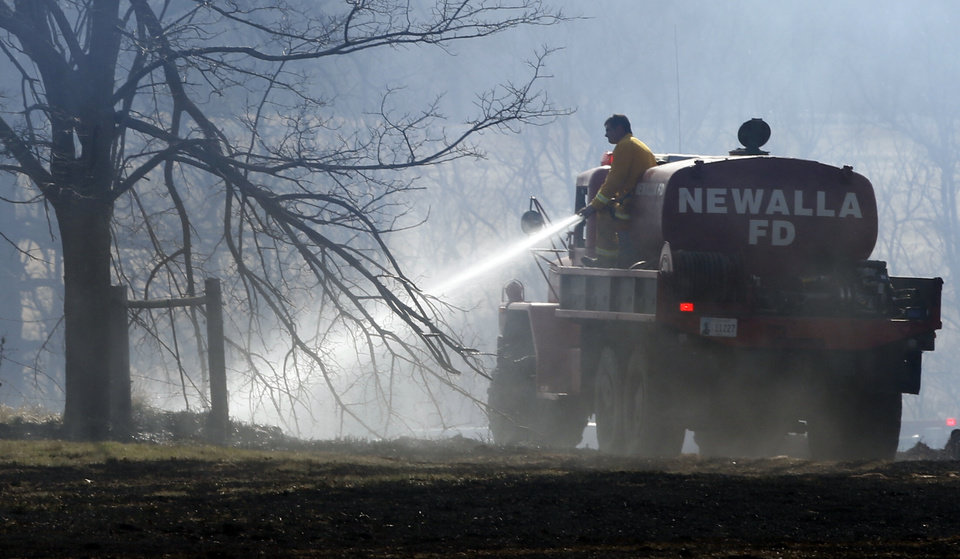 Photo -  Firemen put out a grass fire near SE 74th and Pottowatomie Road on Thursday, March 27, 2014, in Oklahoma City, Okla. Photo by Steve Sisney, The Oklahoman   STEVE SISNEY -  THE OKLAHOMAN