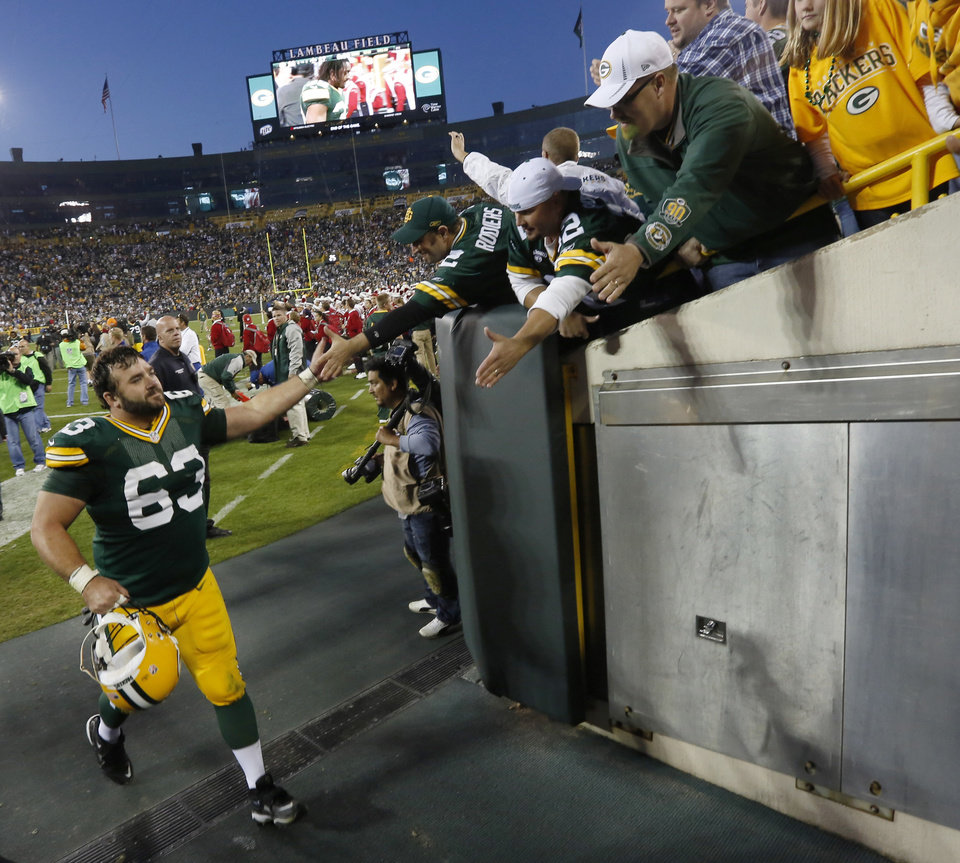 Green Bay Packers center Jeff Saturday high-fives fans after an NFL football game against the New Orleans Saints on Sunday, Sept. 30, 2012, in Green Bay, Wis. The Packers won 28-27. (AP Photo/Mike Roemer)