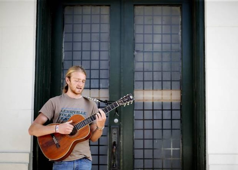"""Photo -  Zach """"Horseshoe"""" Tyndall plays guitar in downtown during the Woody Guthrie Festival in Okemah, Okla., Friday, July 11, 2014. Photo by Sarah Phipps, The Oklahoman"""