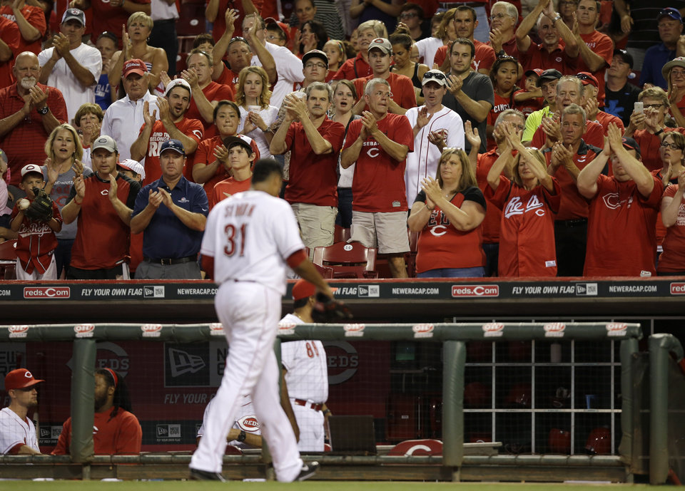 Photo - Cincinnati Reds starting pitcher Alfredo Simon gets a standing ovation as he walks to the dugout after being taken out in the seventh inning of a baseball game against the Chicago Cubs, Wednesday, July 9, 2014, in Cincinnati. Simon pitched six and two-thirds innings, giving up one run, in winning his 12th game of the season 4-1. (AP Photo/Al Behrman)