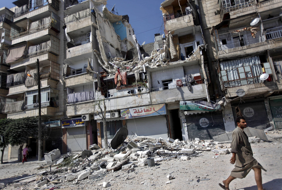 Photo -   A Syrian man walks by a building destroyed in an airstrike in Aleppo city, Syria, Friday, Aug. 17, 2012. Rebel footholds in Aleppo have been the target of weeks of Syrian shelling and air attacks as part of wider offensives by President Bashar Assad's regime. Rebels have been driven from some areas, but the report of clashes near the airport suggests the battles could be shifting to new fronts. (AP Photo/Khalil Hamra)