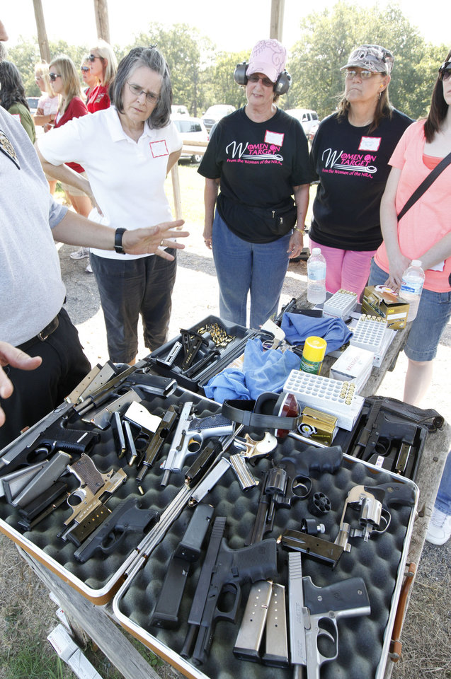 Photo - Women look over a number of handgun options during the annual Women's Only Fun Shoot at the Oklahoma City Gun Club north of Arcadia, OK, Saturday, September 7, 2013,  Photo by Paul Hellstern, The Oklahoman
