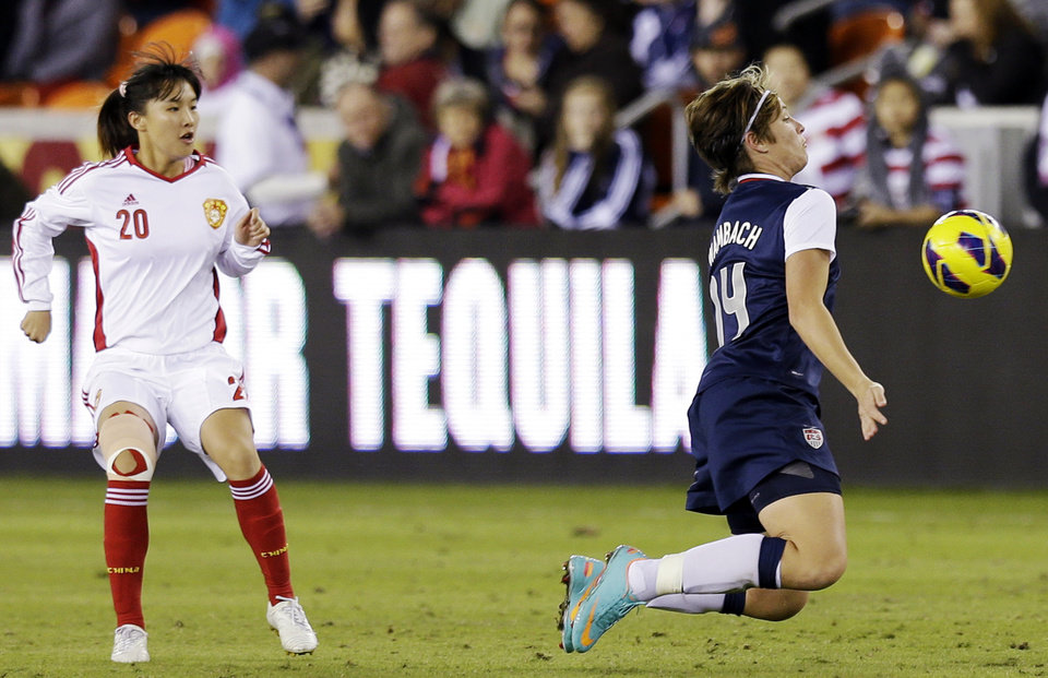 United States' Abby Wambach deflects a ball in front of China's Huang Yini during the second half of an exhibition soccer match, Wednesday, Dec. 12, 2012, in Houston. (AP Photo/David J. Phillip)