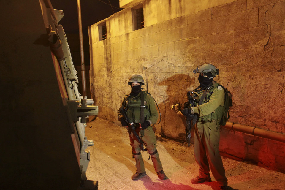 Photo - Israeli soldiers stand guard during a military operation to search for three missing teenagers near the West Bank city of Hebron, Sunday, June 15, 2014. A terror group abducted three teens, including an American, who disappeared in the West Bank, Israel's Prime Minister Benjamin Netanyahu said Saturday, as soldiers searched the territory to find them. (AP Photo/Nasser Shiyoukhi)